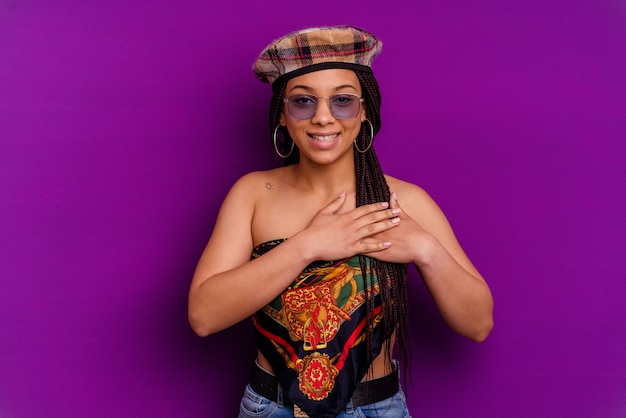 Joven afroamericana la joven afroamericana tiene una expresión amistosa, presionando la palma contra el pecho. concepto de amor.
