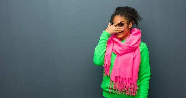 Joven afroamericana con ojos azules avergonzada y riendo al mismo tiempo