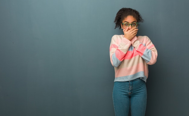 Joven afroamericana con ojos azules sorprendida y sorprendida