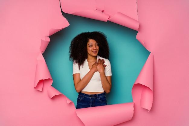 Joven afroamericana en papel rasgado aislado en la pared azul tiene una expresión amistosa, presionando la palma contra el pecho. concepto de amor.