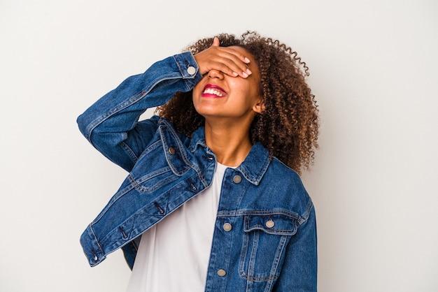 Joven afroamericana con pelo rizado aislado sobre fondo blanco se ríe con alegría manteniendo las manos en la cabeza. concepto de felicidad.