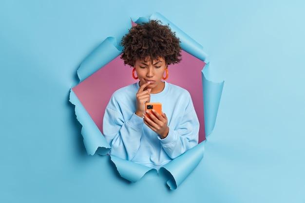 La joven afroamericana de piel oscura desconcertada parece dudosa concentrada en un teléfono inteligente