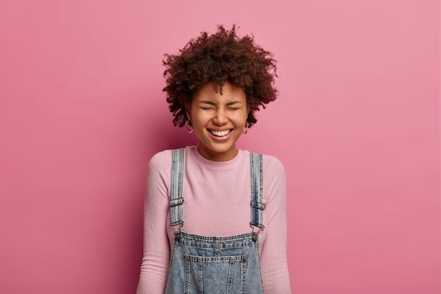Una joven afroamericana positiva sonríe ampliamente, tiene un estado de ánimo optimista, se ríe de algo muy divertido o hilarante, cierra los ojos, escucha una broma loca, se viste de manera informal, se para contra la pared rosa pastel