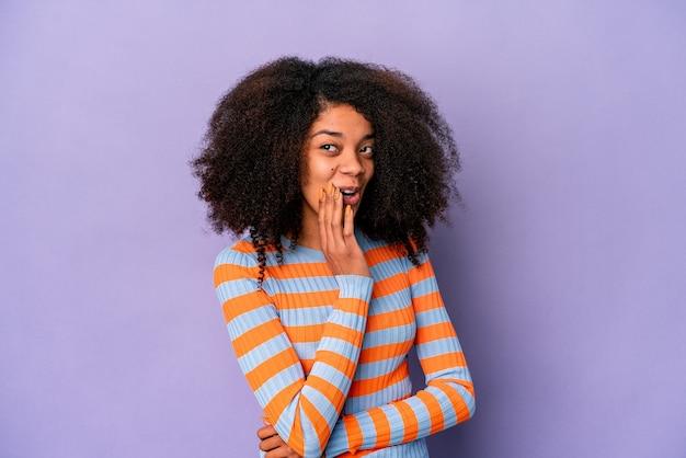 Joven afroamericana rizada aislada sobre fondo púrpura está diciendo una noticia secreta de frenado caliente y mirando a un lado