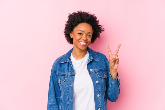 Joven afroamericana sobre un fondo rosa aislado mostrando el signo de la victoria y sonriendo ampliamente.