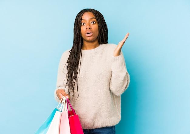 Joven afroamericana sosteniendo una bolsa de compras aislada sorprendida y conmocionada.