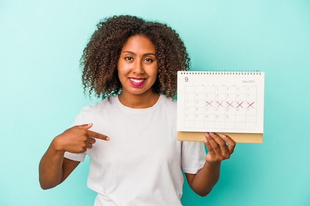 Joven afroamericana sosteniendo un calendario aislado sobre fondo azul persona apuntando con la mano a un espacio de copia de camisa, orgulloso y seguro