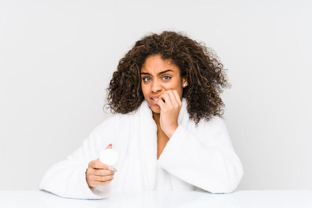 Joven afroamericana sosteniendo una crema hidratante mordiéndose las uñas, nerviosa y muy ansiosa.