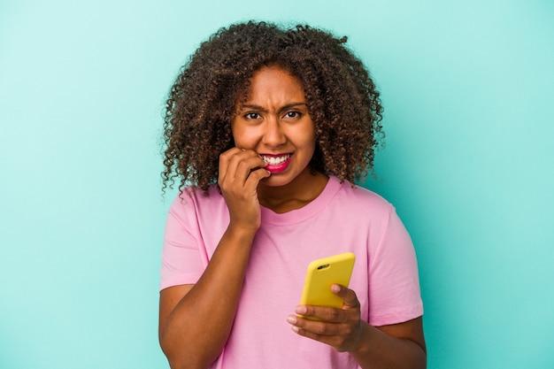 Joven afroamericana sosteniendo un teléfono móvil aislado sobre fondo azul mordiéndose las uñas, nerviosa y muy ansiosa.
