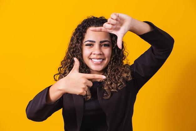 Joven afroamericana vistiendo ropa ejecutiva sonriendo haciendo marco de fotos con las manos y los dedos con una cara feliz. concepto de creatividad y fotografía.