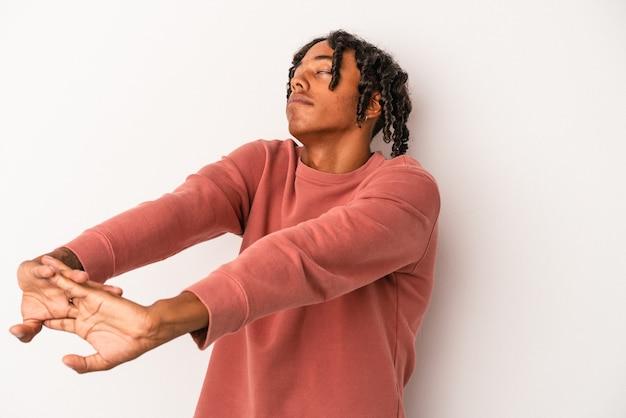 Joven afroamericano aislado sobre fondo blanco estirando los brazos, posición relajada.