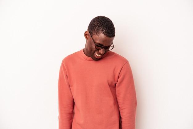Joven afroamericano aislado sobre fondo blanco se ríe y cierra los ojos, se siente relajado y feliz.