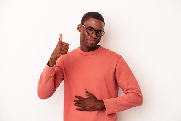 Joven afroamericano aislado sobre fondo blanco toca la barriga, sonríe suavemente, comiendo y concepto de satisfacción.