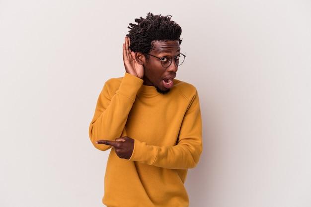 Joven afroamericano aislado sobre fondo blanco tratando de escuchar un chisme.