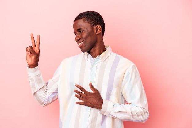 Joven afroamericano aislado sobre fondo rosa tomando un juramento, poniendo la mano en el pecho.