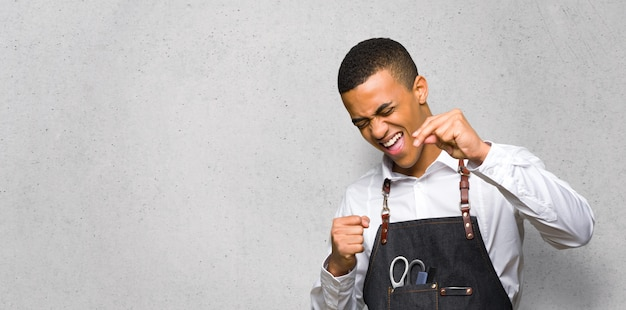 Joven afroamericano barbero disfruta bailando mientras escucha música
