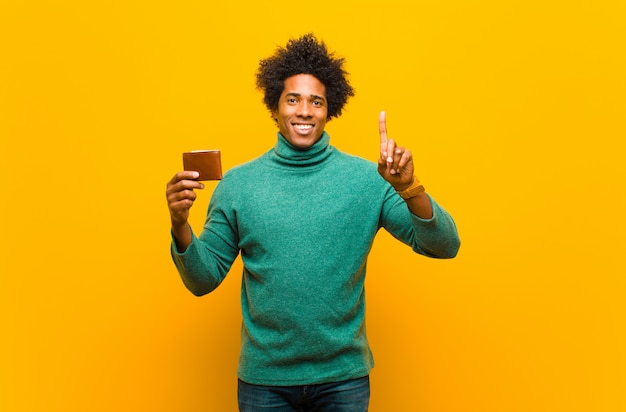 Joven afroamericano con una billetera contra backgrou naranja