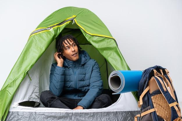 Joven afroamericano dentro de una tienda de campaña verde pensando una idea