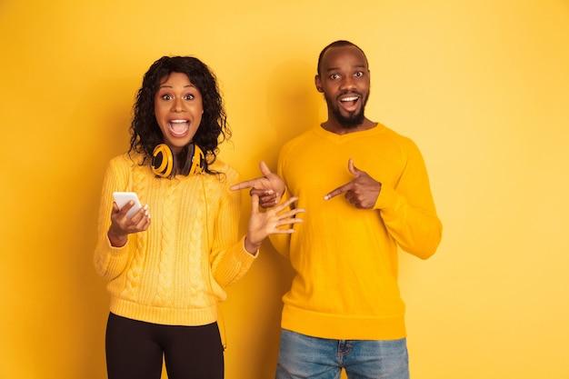 Joven afroamericano emocional y mujer en ropa casual brillante sobre fondo amarillo. hermosa pareja. concepto de emociones humanas, expresión facial, relaciones. sorprendido apuntando en el teléfono inteligente.