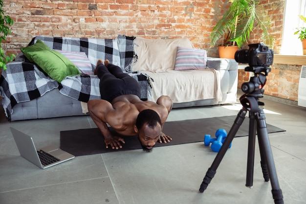 Joven afroamericano enseñando en casa cursos en línea de acondicionamiento físico, estilo de vida aeróbico y deportivo durante la cuarentena, grabando en cámara, transmitiendo
