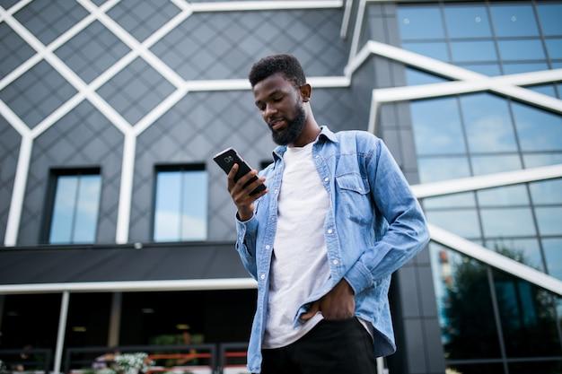 Joven afroamericano enviando mensajes de texto celular caminando en la ciudad