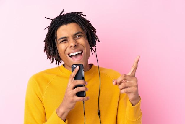 Joven afroamericano escuchando música sobre pared rosa