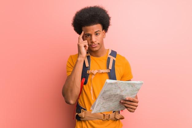 Joven afroamericano explorador hombre sosteniendo un mapa pensando en una idea