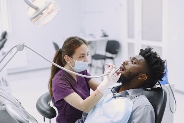 Joven afroamericano. guy visitando el consultorio del dentista para la prevención de la cavidad bucal. médico hombre y mujer mientras chequeo de dientes.