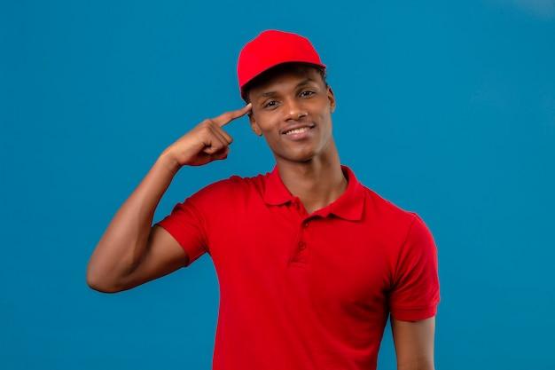 Joven afroamericano inteligente buscando repartidor vistiendo polo rojo y gorra sonriendo y apuntando sobre su cabeza de pie sobre azul aislado