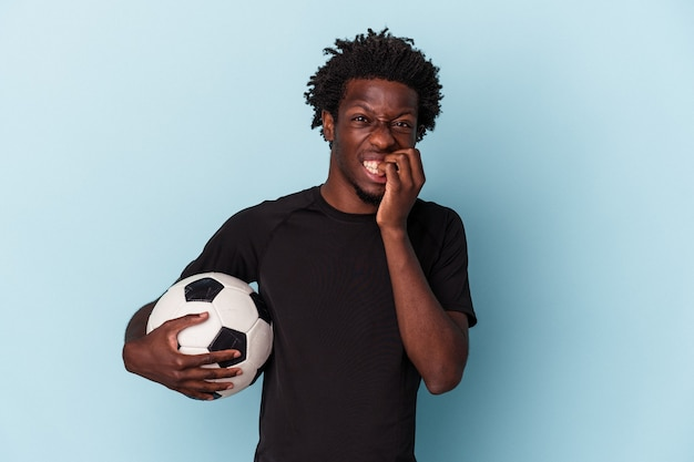 Joven afroamericano jugando al fútbol aislado sobre fondo azul mordiéndose las uñas, nervioso y muy ansioso.