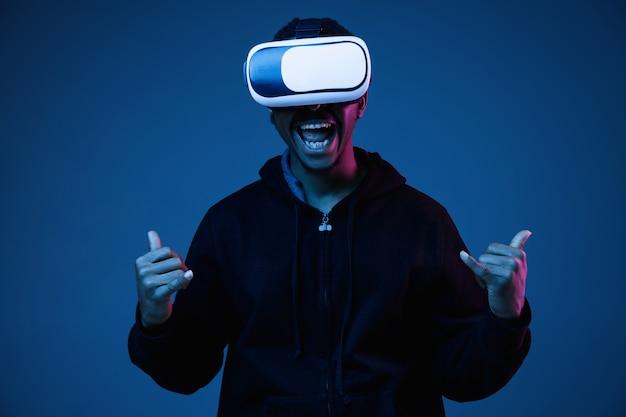 Joven afroamericano jugando con gafas vr en luz de neón en gradiente.