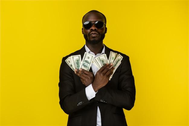 Joven afroamericano de lujo con barba tiene mucho dinero en ambas manos con gafas de sol y traje negro