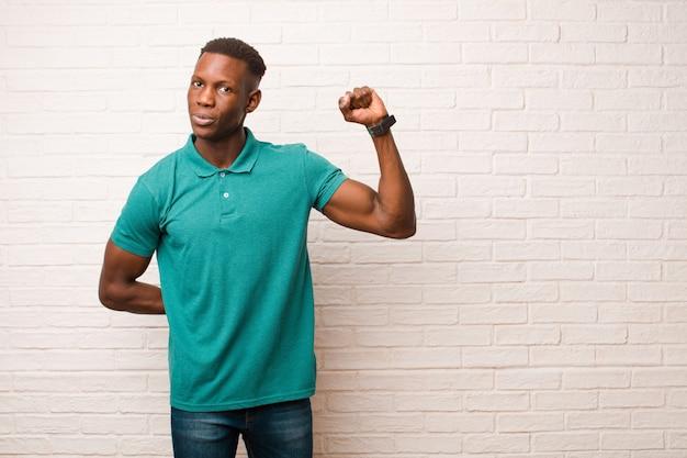 Joven afroamericano negro se siente serio, fuerte y rebelde, levantando el puño, protestando o luchando por la revolución en la pared de ladrillo