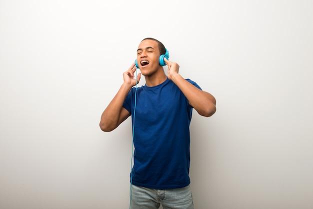 Joven afroamericano en pared blanca escuchando música con auriculares