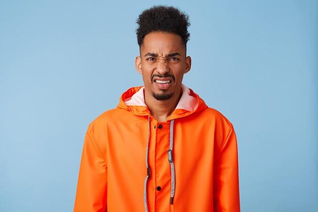 Un joven afroamericano de piel oscura insatisfecho viste un impermeable naranja, se siente muy molesto, frunce el ceño y mira con disgusto, se pone de pie.
