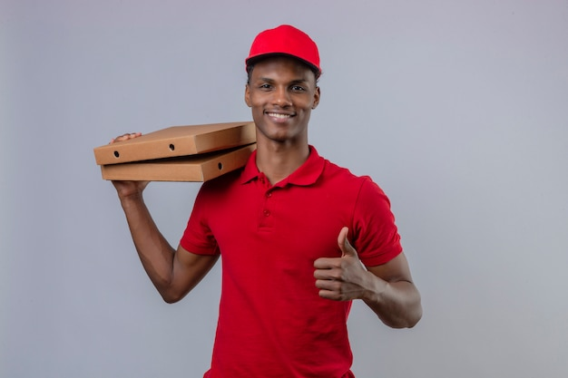 Joven afroamericano repartidor vistiendo polo rojo y gorra con pila de cajas de pizza mostrando el pulgar hacia arriba y sonriendo sobre blanco aislado