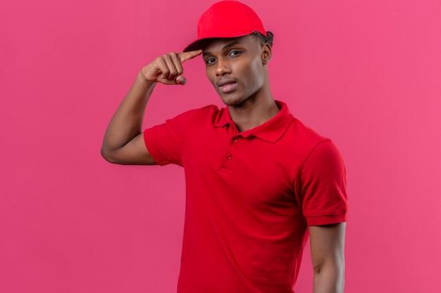 Joven afroamericano repartidor vistiendo polo rojo y gorra con sonrisa en la cara apuntando a la cabeza con el dedo sobre rosa aislado