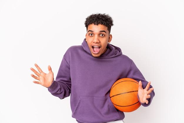 Joven afroamericano rizado aislado jugando baloncesto sorprendido y conmocionado.