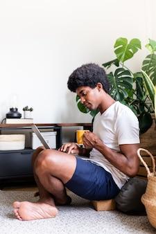 Joven afroamericano sentado en el suelo con café con portátil en su apartamento vertical