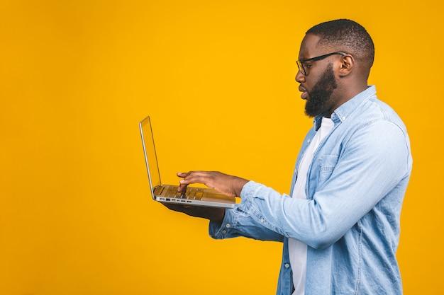 Joven afroamericano serio de pie y usando la computadora portátil