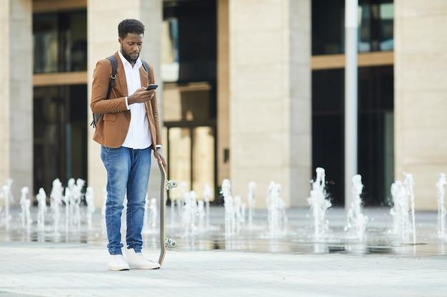 Joven afroamericano con smartphone en la ciudad