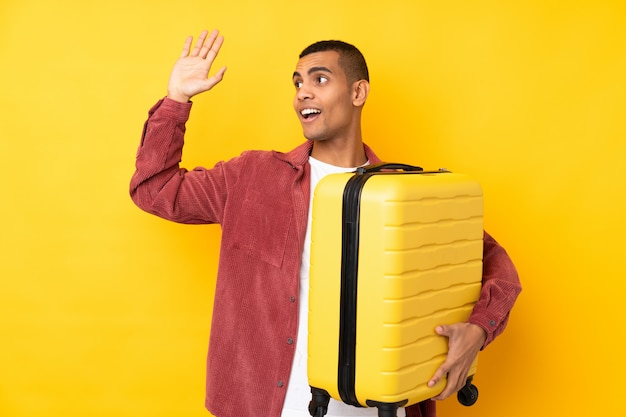Joven afroamericano sobre pared amarilla aislada en vacaciones con maleta de viaje y saludando