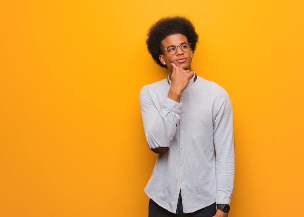 Joven afroamericano sobre una pared naranja dudando y confundido