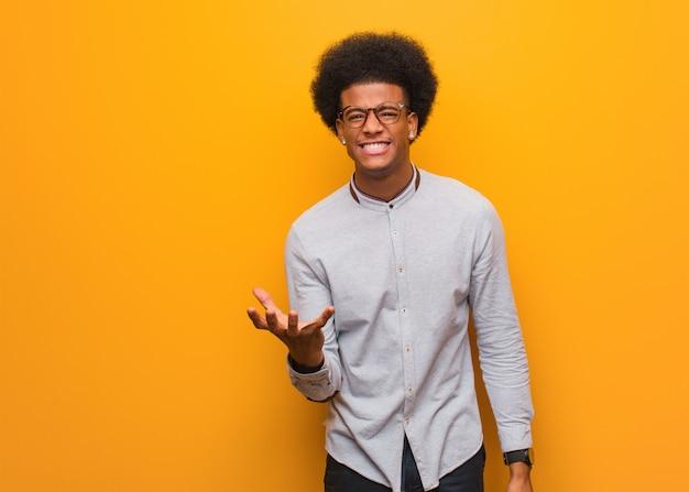 Joven afroamericano sobre una pared naranja muy asustado y asustado