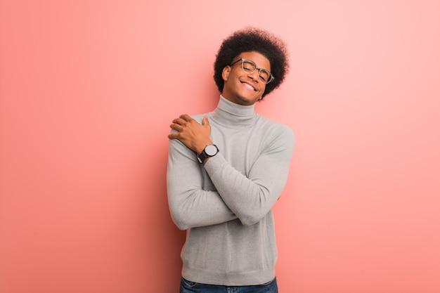 Joven afroamericano sobre una pared rosa dando un abrazo