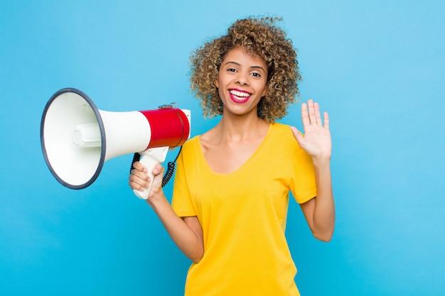 Joven afroamericano sonriendo feliz y alegremente, saludando con la mano, dándole la bienvenida y saludándolo, o diciéndole adiós con un megáfono