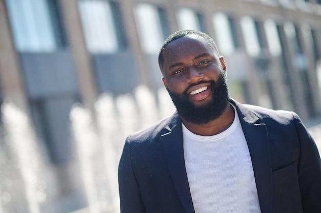 Joven afroamericano sonriendo y mirando contento