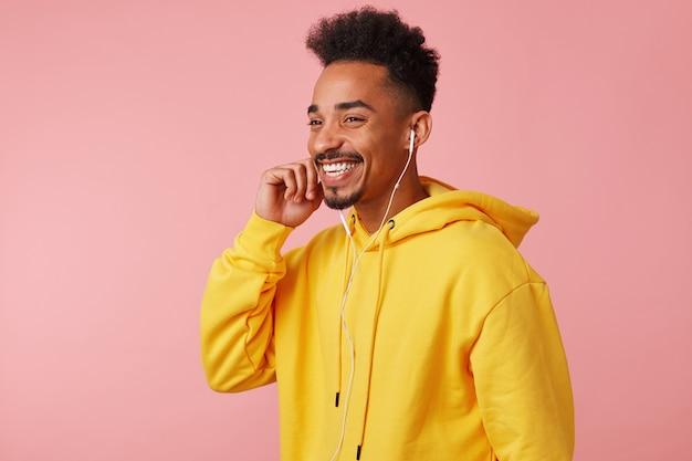 Joven afroamericano sonriente feliz en sudadera con capucha amarilla, hablando con su amigo por auriculares, escuchó una broma muy divertida y se rió, de pie con copyspace.