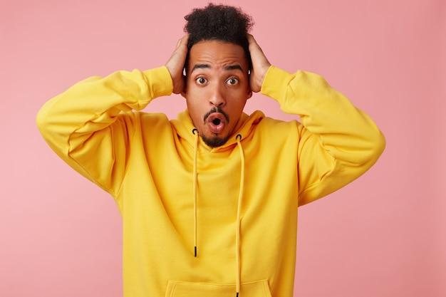 Joven afroamericano sorprendido con sudadera con capucha amarilla, sosteniendo su cabeza, su equipo de fútbol favorito falló un gol, mirando con los ojos y la boca bien abiertos, se levanta.