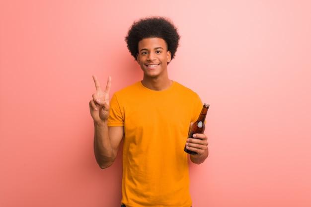 Joven afroamericano sosteniendo una cerveza mostrando el número dos